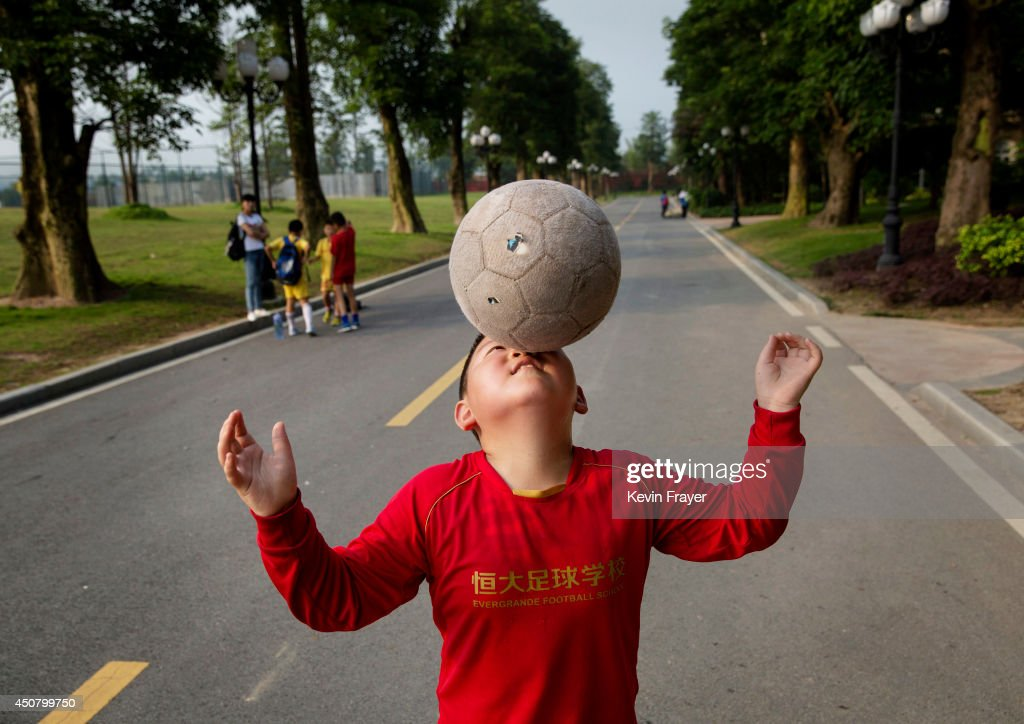 A young Chinese student balances the ball on his nose as he walks to a training match at the Evergrande International Football School on June 14, 2014 near Qingyuan in Guangdong Province, China. The sprawling 167-acre campus is the brainchild of property tycoon Xu Jiayin, whose ambition is to train a generation of young athletes to establish China as a football powerhouse. The school is considered the largest football academy in the world with 2400 students, more than 50 pitches and a squad of Spanish coaches through a partnership with Real Madrid.