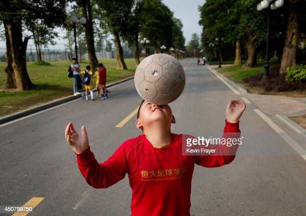 A young Chinese student balances the ball on his nose as he walks to a training match at the Evergrande International Football School on June 14 2014...