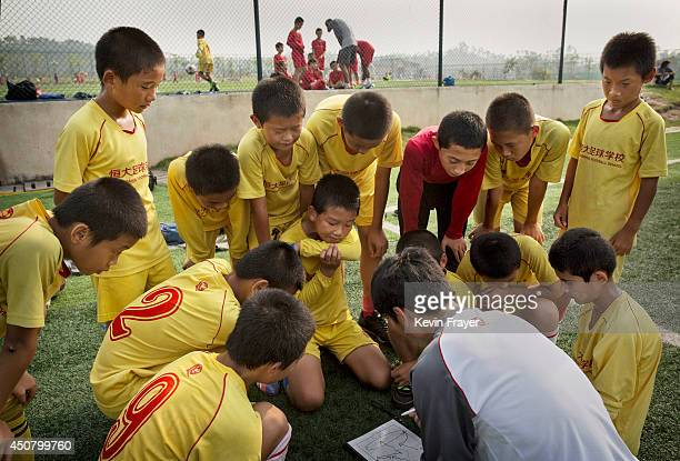 Young Chinese students listen to instruction from a coach prior to a training match at the Evergrande International Football School on June 14 2014...