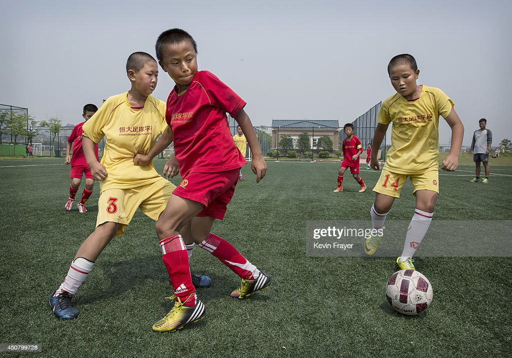 Young Chinese students play during a match on a practice pitch at the Evergrande International Football School on June 14, 2014 near Qingyuan in Guangdong Province, China. The sprawling 167-acre campus is the brainchild of property tycoon Xu Jiayin, whose ambition is to train a generation of young athletes to establish China as a football powerhouse. The school is considered the largest football academy in the world with 2400 students, more than 50 pitches and a squad of Spanish coaches through a partnership with Real Madrid.