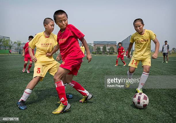 Young Chinese students play during a match on a practice pitch at the Evergrande International Football School on June 14 2014 near Qingyuan in...