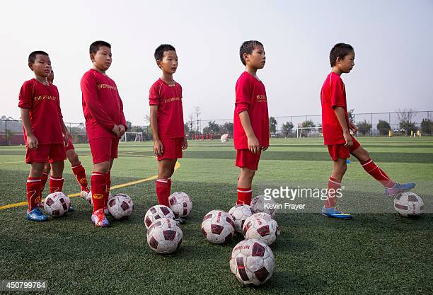 Young Chinese students wait to kick during training at the Evergrande International Football School on June 14 2014 near Qingyuan in Guangdong...