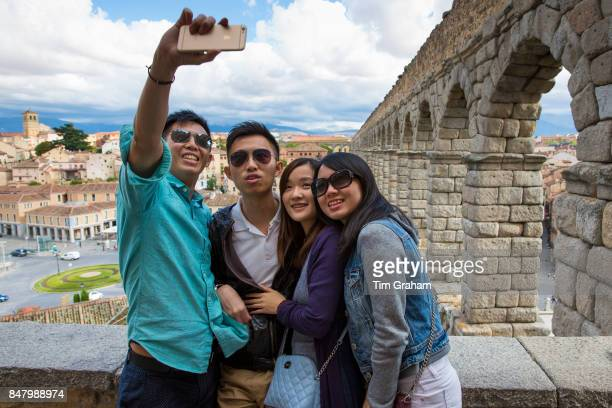 Young Chinese tourists taking selfie photographs with iPhone smartphone at famous Roman aqueduct Segovia Spain