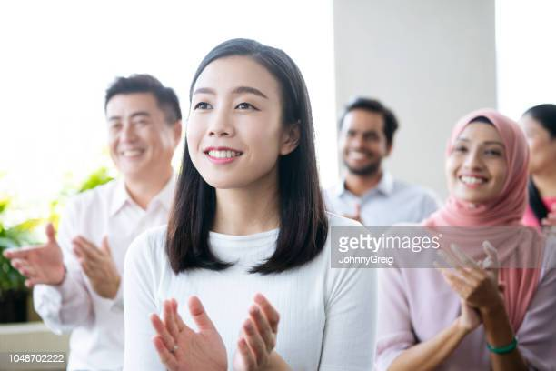young chinese woman at conference clapping and smiling - attending stock pictures, royalty-free photos & images