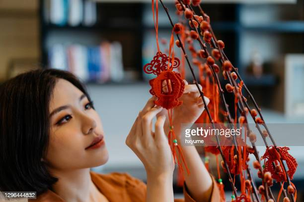 young chinese woman hanging decoration and prepare for chinese new year - differential focus stock pictures, royalty-free photos & images
