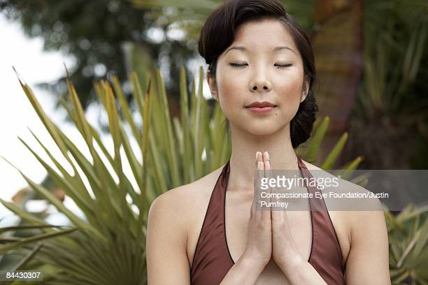 Young Chinese Woman in front of palms, meditating.
