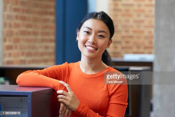 young chinese woman looking at camera in office - businesswoman stock pictures, royalty-free photos & images
