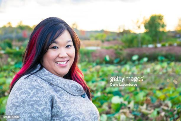a young chinese woman outside in the fall. - fat asian woman stock pictures, royalty-free photos & images