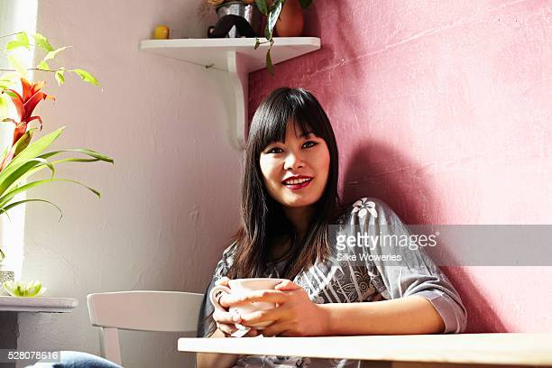 young chinese woman sitting in her kitchen and drinking tea