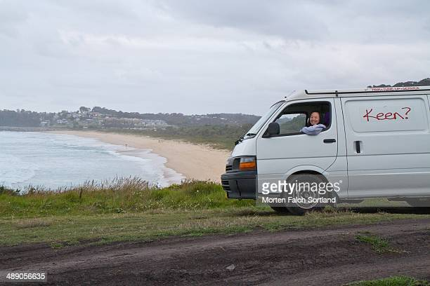 Young Chinese woman sitting inside car above the beach in Narooma Eurobodalla just before sunset
