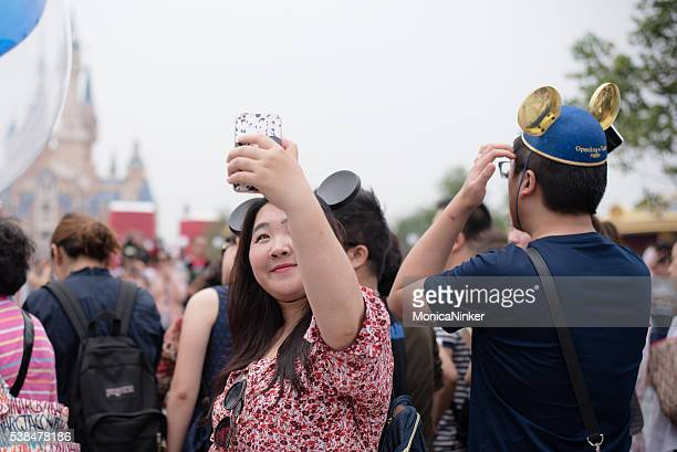 Young chinese woman taking a Selfie in Shanghai, Disneyland