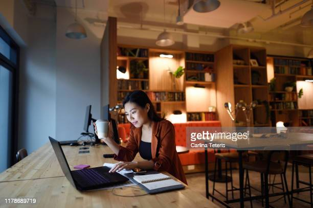 Young Chinese woman working on her laptop late at night