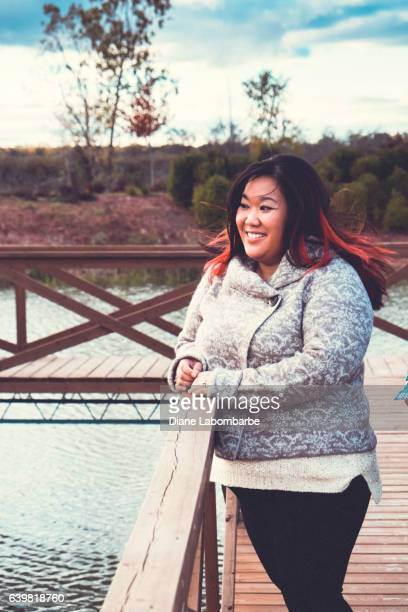 A Young Chinese Womans Stands On A Bridge In A Park