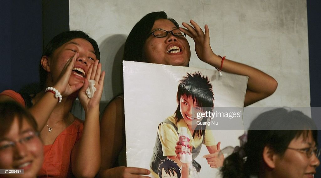 Young Chinese women holds a poster of 'Super Girl Voice' during a recording at Hunan Satellite TV station on June 21, 2006 in Changsha city, Hunan province of China. 'Super Girl Voice' is an entertainment program produced to select new girl stars. More and more Chinese youth are entering TV entertainment shows in an attempt to become famous and new pop idols.