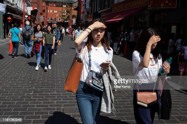 Young Chinese women shielding their eyes from the sun on Gerrard Street Soho also known as Chinatown in London United Kingdom The present Chinatown...