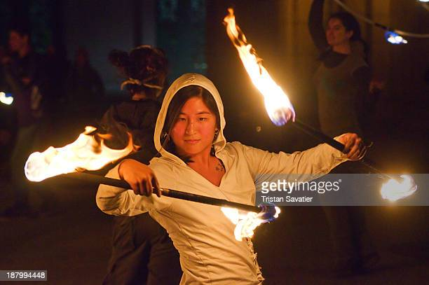 Young Chinese-American woman in a fire spinning performance. She is using two fire staves. Fire performers use ropes, staves, 'poi' and other 'flow...