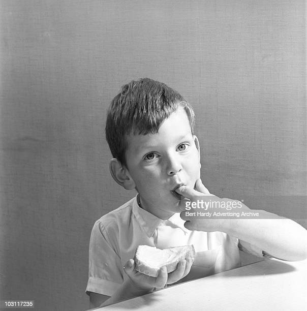 Young Chris Steibelt eats a slice of buttered bread at a studio in Bickley, London, 5th November 1960.