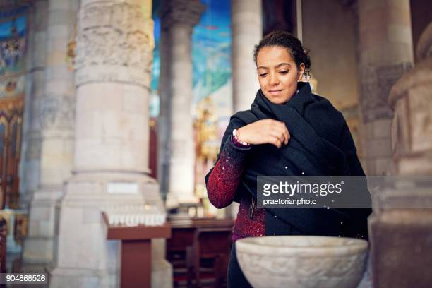 Young christian girl is praying in the cathedral