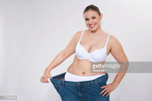 young chubby woman with oversized pant, portrait - big fat white women stockfoto's en -beelden