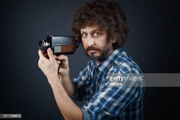 若い撮影監督は、それでシーンを撮影する前に、彼の昔ながらのフィルムカメラを調整します - film director ストックフォトと画像