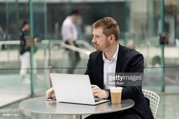 young city businessman at sidewalk cafe looking away - businesswear stock pictures, royalty-free photos & images
