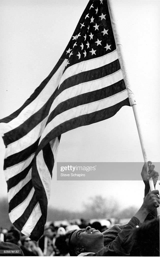 Young civil rights activist waves an American flag during the Selma to Montgomery Civil Rights Marches. There were three march attempts, the first was coined 'Bloody Sunday' after it was marked by violence against the civil rights activists by the local and state police. The third march attempt was successful in reaching the Alabama state capital in Montgomery.
