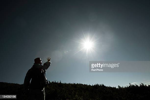 young climber looking the sun at the mountain