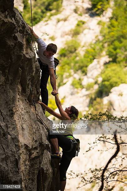 Young climbing couple helping each other in the rock wall