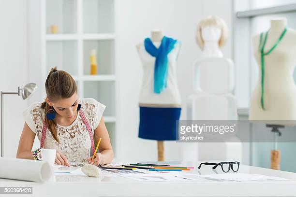 Ropa de diseño joven trabajando en bocetos en su oficina.