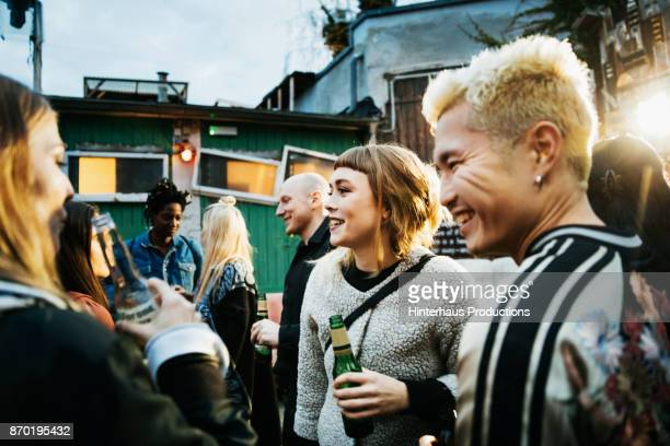young clubgoers drinking and catching up at open air nightclub - asian drink stock photos and pictures