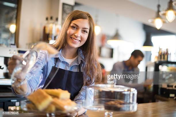 Cafetería joven camarera muestra su flapjacks