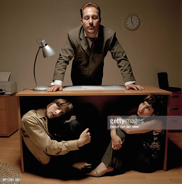 Young colleagues hiding under desk from businessman