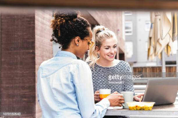young colleagues sitting outdoors, working together, having lunch - lunch stock pictures, royalty-free photos & images