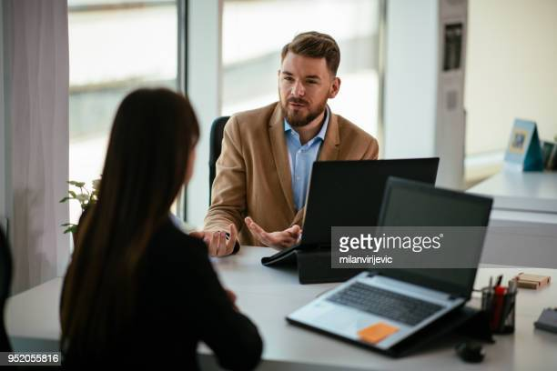 Young colleagues talking to each other in the office