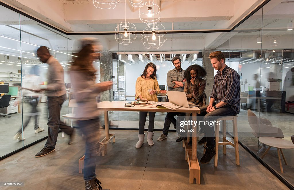 Young colleagues using laptop in the office among blurred people. : Stock Photo