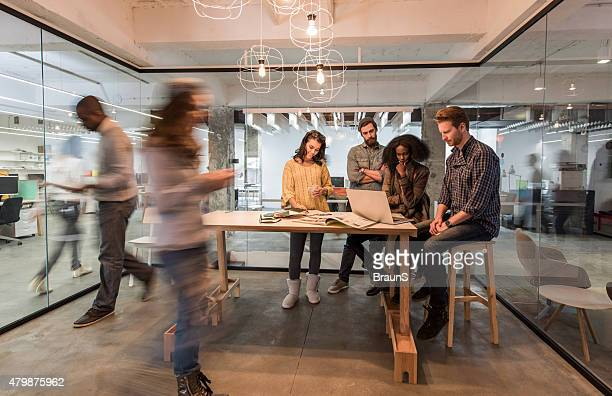 young colleagues using laptop in the office among blurred people. - new business stock pictures, royalty-free photos & images
