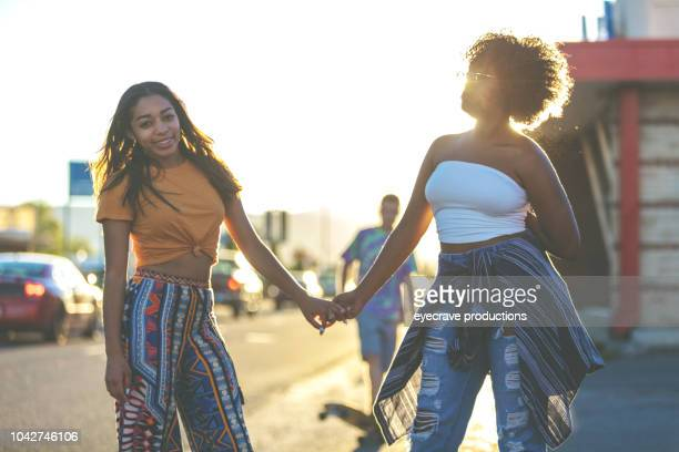 Young College Age Ethnic Female and Male Students On Urban American Street at Sunset