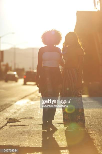 Young College Age Ethnic Females Students On Urban American Street at Sunset