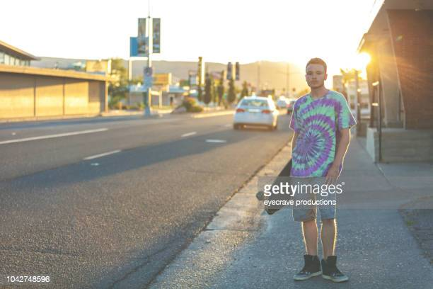 Young College Age Male Student On Urban American Street Skateboarding at Sunset