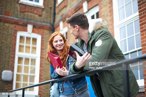 young college student couple leaning against campus handrail - campus stock pictures, royalty-free photos & images