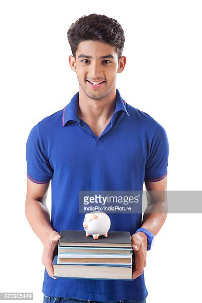young college student holding stack of books with a small piggy bank