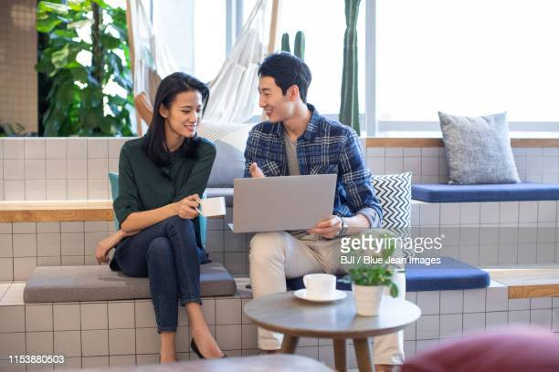young college students using laptop - 衣服 トップス ストックフォトと画像