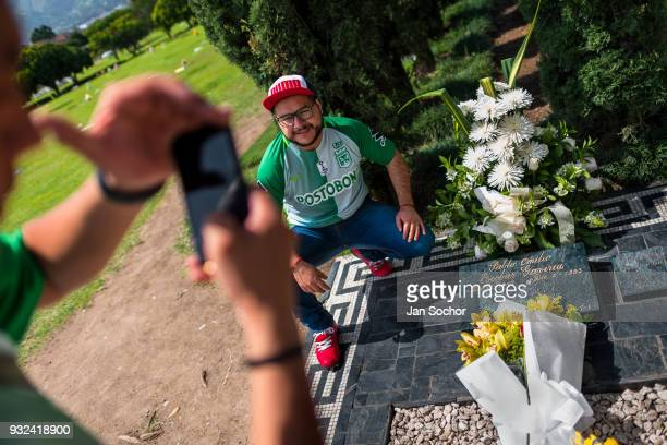 Young Colombian men take snapshots of themselves while visiting the tomb of the drug lord Pablo Escobar at the cemetery of Montesacro in Itagüí...