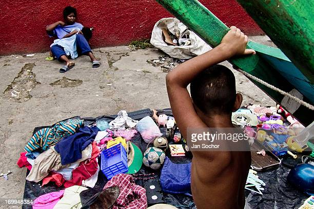 A young Colombian mother with her babygirl sells rummage and used clothes from garbage dumps in the slum of Calvario on 3 April 2004 in Cali Colombia...