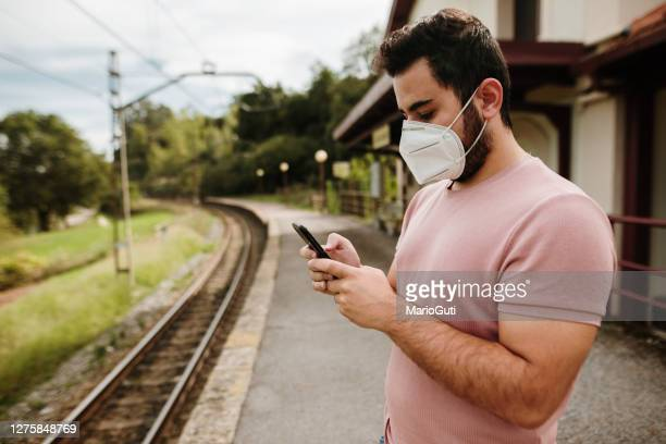 young commuter waiting in a railroad station wearing a face mask - facial hair stock pictures, royalty-free photos & images