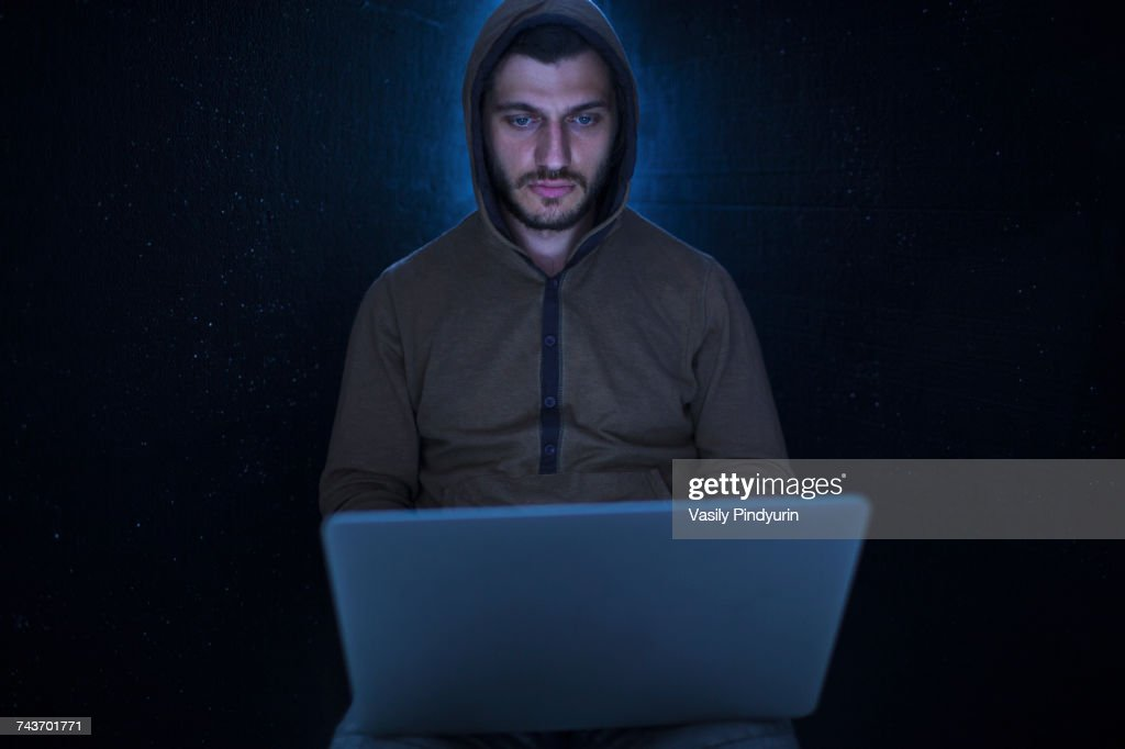 Young computer hacker wearing hooded shirt using laptop against black background : Stock Photo