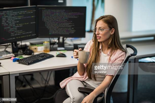 young computer programmer taking a coffee break in the office. - coding stock pictures, royalty-free photos & images