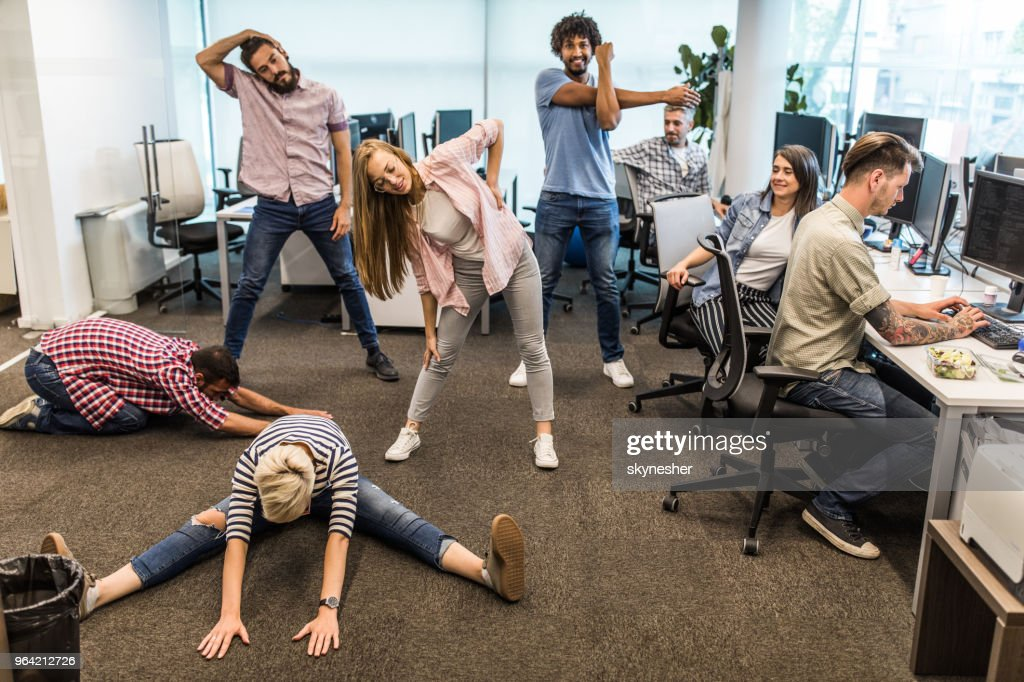 Group of programmers exercising on a break in the office. : Stock Photo
