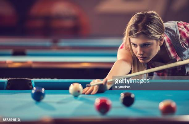 Young concentrated woman playing snooker in a bar.