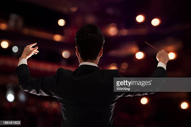 young conductor with baton raised at a performance, rear view - concert hall stock pictures, royalty-free photos & images
